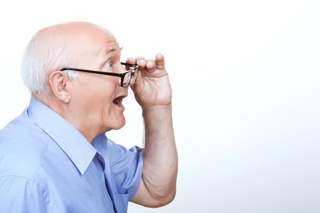 Foto de What a surprise. Surprised grandfather holding the hand on  glasses and showing wonder while standing half face - Imagen libre de derechos