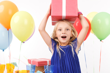 Photo for Pleasant young girl holding present on her head - Royalty Free Image