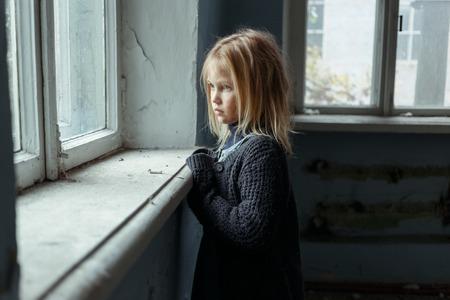 Foto de Close up of depressed poor little girl standing near window and looking aside while feeling miserable - Imagen libre de derechos