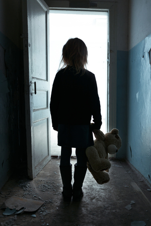 Photo pour Poor sad miserable little girl holding her toy and standing turned back while leaving the room - image libre de droit