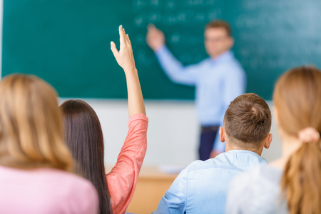 Photo for Female young student in a group raises her arm in order to answer the question. - Royalty Free Image