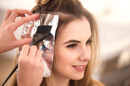 Foto de Make it properly. Beautiful charming woman sitting in the hairdressing salon while professional hairdresser dyeing her hair - Imagen libre de derechos