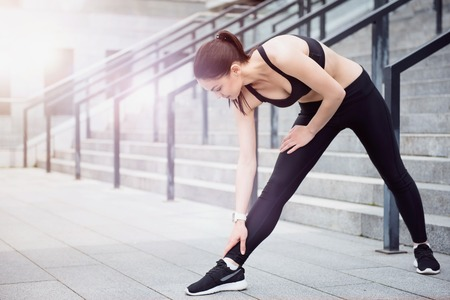 Photo pour Way to keep fit. Pretty young flexible girl wearing a sportswear and doing stretching exercises while waiting for training. - image libre de droit