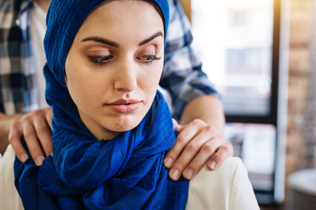Photo for Muslim woman beign herrased by representative of another group - Royalty Free Image