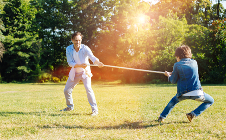 Photo for Adorable kid and his dad finding out who being stronger - Royalty Free Image