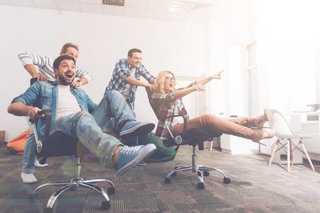 Foto de Cheerful colleagues having fun in office chairs - Imagen libre de derechos