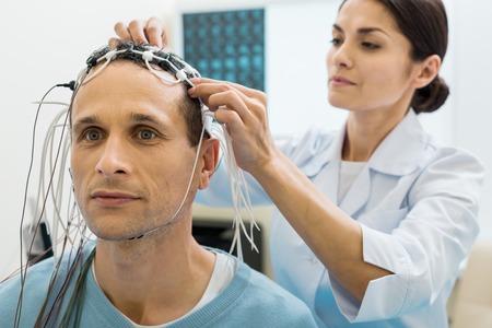 Foto de Female doctor fixing electrodes on head of patient - Imagen libre de derechos