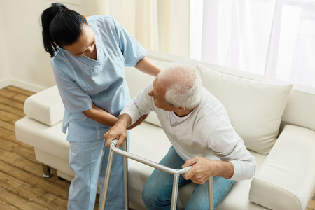 Foto de Pleasant friendly caregiver doing her job - Imagen libre de derechos