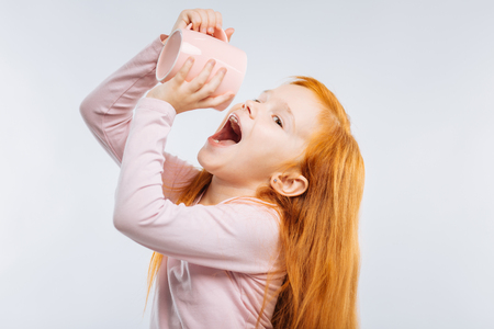 Photo for Want to drink. Attractive child opening mouth and looking sideways while standing in semi position isolated on grey - Royalty Free Image