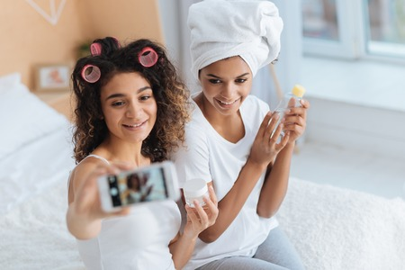 Photo for One more shot. Selective focus on radiant young ladies smiling cheerfully while sitting on a bed and posing for a self portrait picture at home. - Royalty Free Image