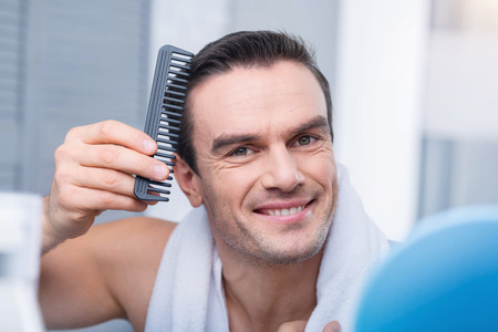 Foto de Perfect hair cut. Pleasant gorgeous cheerful man combing hair  smiling to the camera and standing against the blurred background - Imagen libre de derechos