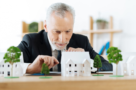 Foto de Very attentive. Clever experienced reliable real estate agent sitting in his office and looking attentively at the model of a wonderful house in the countryside while planning how to sell it - Imagen libre de derechos