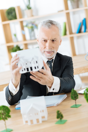 Foto de Nice work. Clever experienced worker of a real estate agency sitting in his office with a wonderful miniature of a house in his hands and looking attentive while thinking about it - Imagen libre de derechos