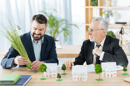 Foto de Funny activity. Friendly colleagues in a real estate agency sitting at the table and discussing their working day while looking at the lovely bunch of herbs and smiling - Imagen libre de derechos
