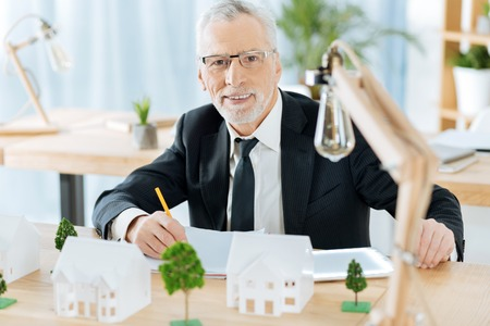 Foto de Confident worker. Clever attentive responsible worker of a real estate agency sitting at the table with lovely miniature houses and trees by his side and making important notes - Imagen libre de derechos