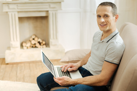 Foto de Feeling good. Young smart handsome man looking positive while sitting on a soft sofa with a modern convenient laptop on his knees and smiling - Imagen libre de derechos