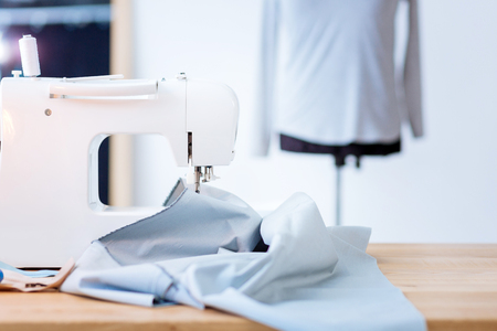 Foto de Sewing equipment. Convenient professional sewing machine standing on a table in a popular atelier with a big piece of light fabric being placed on it - Imagen libre de derechos