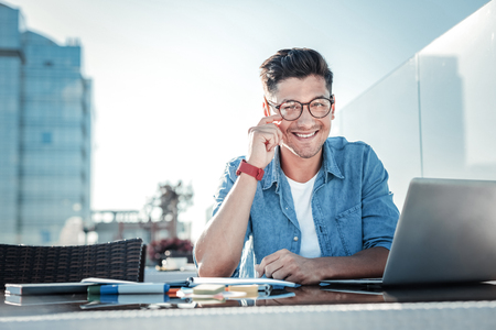 Photo for Waist up shot of a cheerful self employed man sitting at his laptop and looking into the camera with a broad smile on his face while working in a cafe. - Royalty Free Image