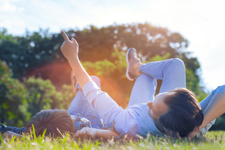 Photo pour Imparting knowledge. Adorable moment of thoughtful father pointing toward a blue sky and telling his son a story while both lying in the grass and chatting. - image libre de droit