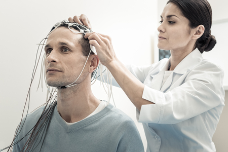 Foto de Brain scanning. Professional serious female doctor standing behind her patient and purring electrodes on his head while preparing him for electroencephalogram - Imagen libre de derechos