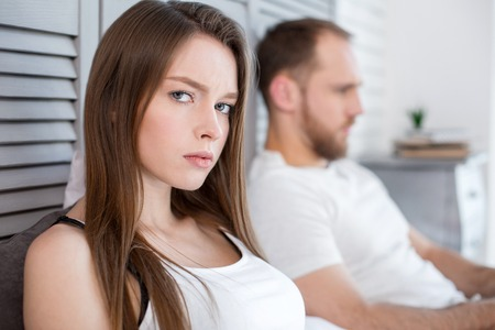 Foto de So lonely. Attractive unsmiling long-haired young woman feeling lonely and her man being next to her and paying no attention to her - Imagen libre de derechos
