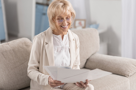 Foto de Joyful glad mature businesswoman wearing glasses while examining papers and grinning - Imagen libre de derechos