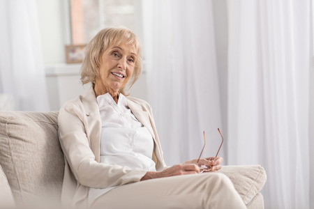 Foto de Merry jolly mature woman posing on couch while thinking and relaxing - Imagen libre de derechos