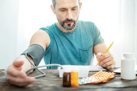 Foto de Sad disappointed deep man measuring pulse by the table looking down and recording results. - Imagen libre de derechos