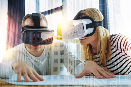 Foto de Smart colleagues. Clever experienced young engineers sitting at the table with modern virtual reality glasses on their heads and looking at the important drawing on the table - Imagen libre de derechos