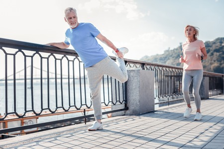Photo pour Sport for everyone. Satisfied unshaken senior man spending time on fresh air holding by the railing doing stretching exercises. - image libre de droit