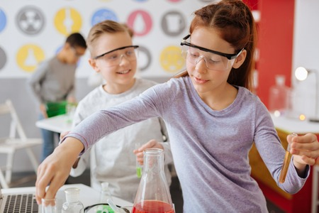 Foto de Best students. Diligent female teenage student in safety goggles mixing chemicals during chemistry class while her classmate watching her do so - Imagen libre de derechos
