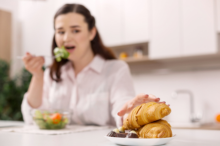 Photo pour Harsh diet. Disturbed gloomy woman stretching for croissant while eating salad - image libre de droit