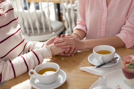 Photo pour Best granny. Loving caring granddaughter holding hands with her granny while having tea - image libre de droit