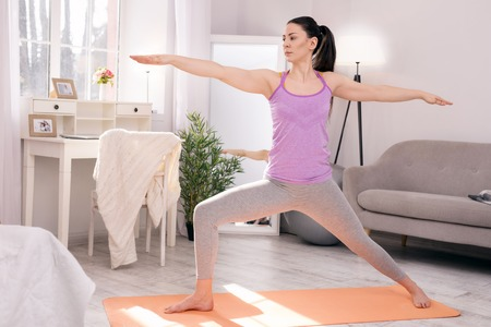 Photo pour Staying fit. Beautiful concentrated woman standing on the carpet and doing some exercises - image libre de droit