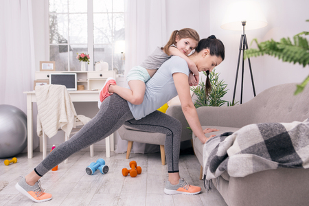 Foto de In high spirits. Determined athletic mother training at home and holding her daughter on her back - Imagen libre de derechos