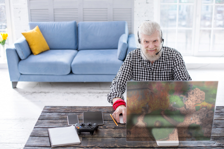 Photo for Exciting game. Pleasant senior man sitting at the table and enjoying playing a multiplayer online game with his friends - Royalty Free Image