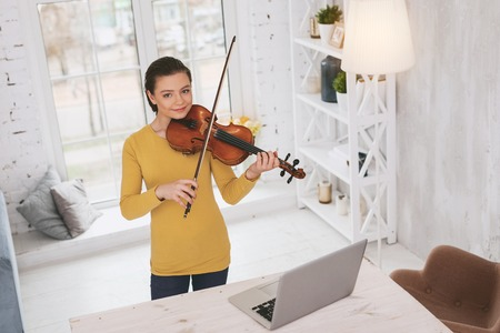 Foto de Beautiful brunette keeping smile on face while playing the violin - Imagen libre de derechos