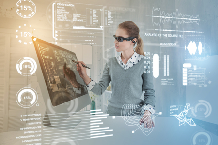 Foto für Clever woman. Experienced database administrator carefully touching the screen with a stylus while working in virtual reality glasses - Lizenzfreies Bild