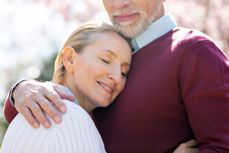 Foto de I feel safe. Delighted aged woman closing her eyes while feeling safe near her husband - Imagen libre de derechos