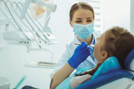 Foto de Open mouth. Competent dentist using instrument while examining her visitor - Imagen libre de derechos