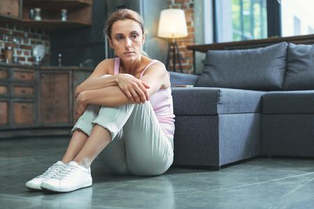 Foto de Unexplained sadness. Desperate mature woman sitting on floor and hugging knees - Imagen libre de derechos
