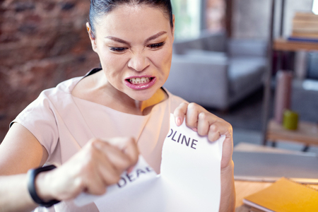 Foto de Stress management. Wrathful female employee tearing paper and posing on blurred background - Imagen libre de derechos