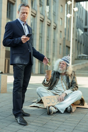 Photo pour Rich and poor. Elderly rich successful businessman feeling helpful while giving some money to poor man - image libre de droit
