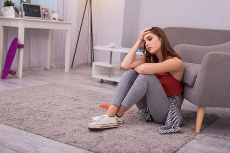 Photo for Miss him. Mournful teen girl touching head and sitting on floor - Royalty Free Image