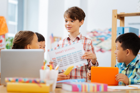 Photo for Easy task. Excited smart boy holding a table in his hands while teaching others - Royalty Free Image