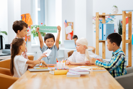 Photo for Games. High-spirited kids playing a game while being in a classroom - Royalty Free Image