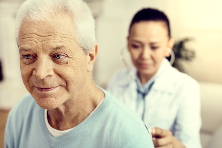 Photo for Preventive measures. Selective focus on a cheerful gentleman attending his physician and checking his lungs during a checkup. - Royalty Free Image