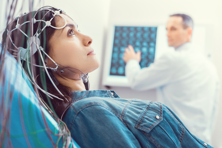 Photo for Hoping for better. Side view on a worried young lady looking into vacancy and thinking while undergoing an electroencephalography procedure at a laboratory. - Royalty Free Image