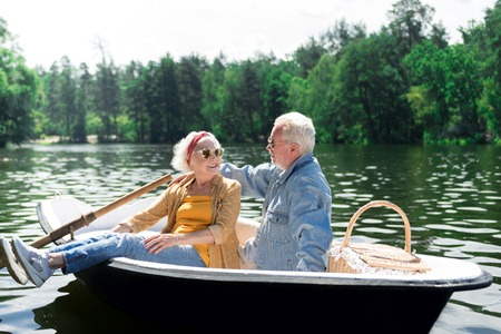 Photo pour Talk in boat. Calm positive senior woman turning to the husband while sitting in the boat near him - image libre de droit
