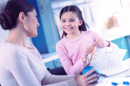 Foto de Happy pupil. Cheerful young woman looking at her smiling daughter while checking her homework - Imagen libre de derechos